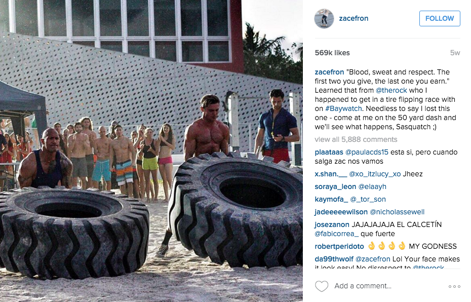 Zac Efron Instagram Pic of him vs the Rock in a tire flip contest on the set of Baywatch.